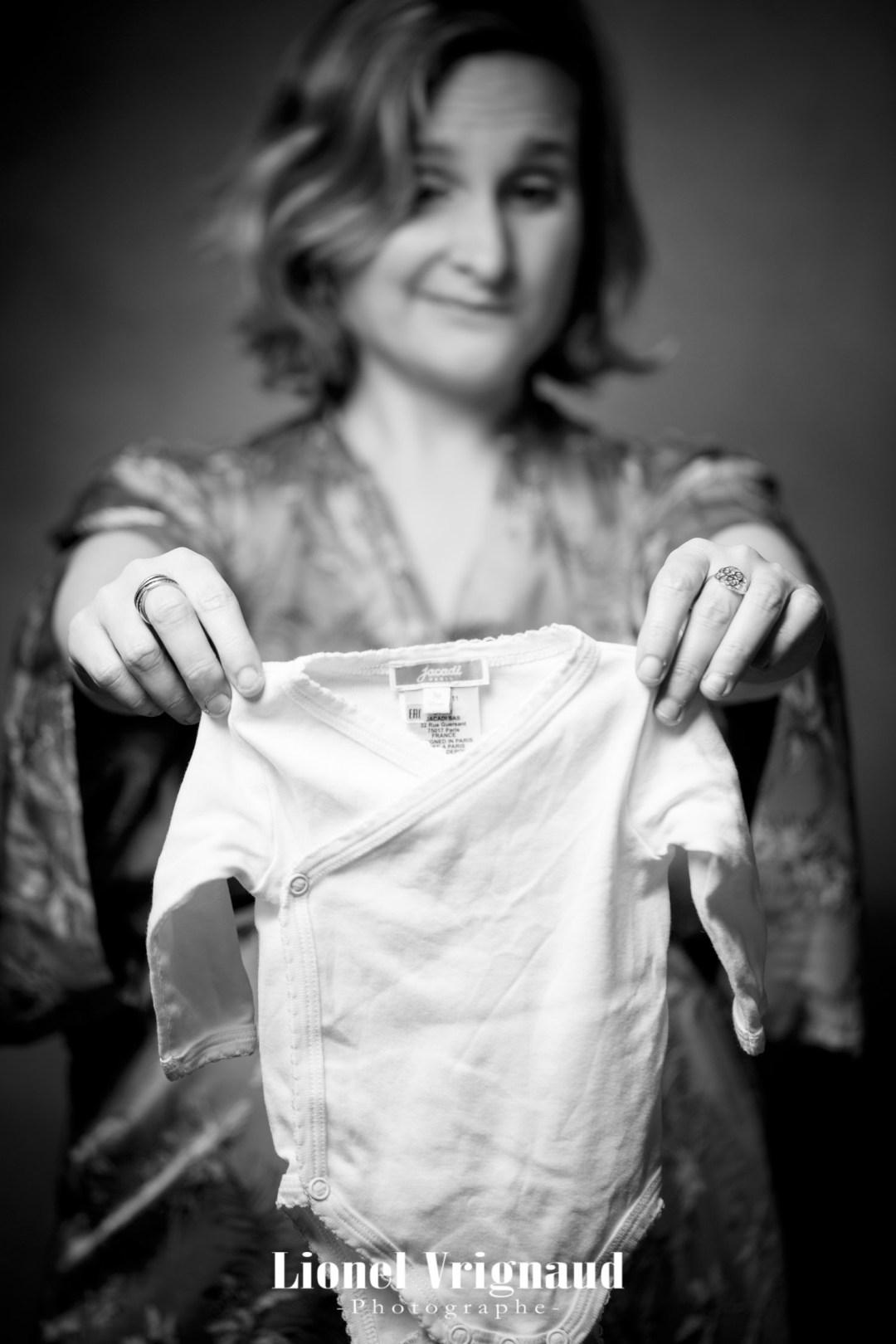 Une femme enceinte tient le vêtement de son futur bébé