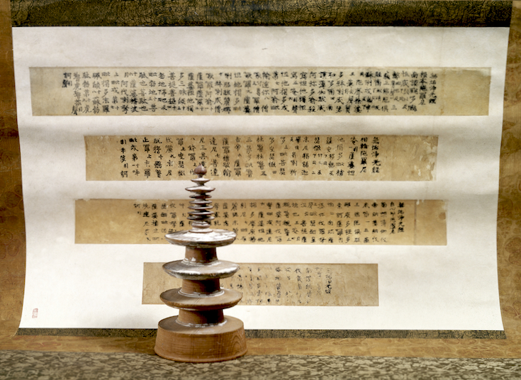 A small stupa stands in front of four pages of printed scripture.