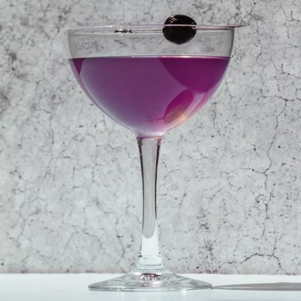 Purple-hued Aviation cocktail in a coupe with a cherry garnish