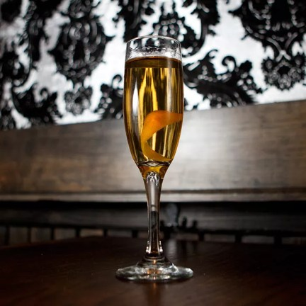 gold-colored La Tour Eiffel cocktail in a Champagne flute with a floating lemon twist, served on a wooden table with black-and-white wallpaper in the background