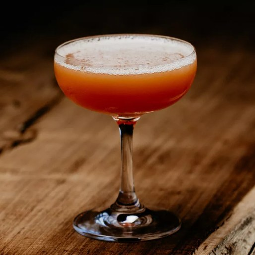 Red-orange Lion's Tail cocktail in a coupe glass