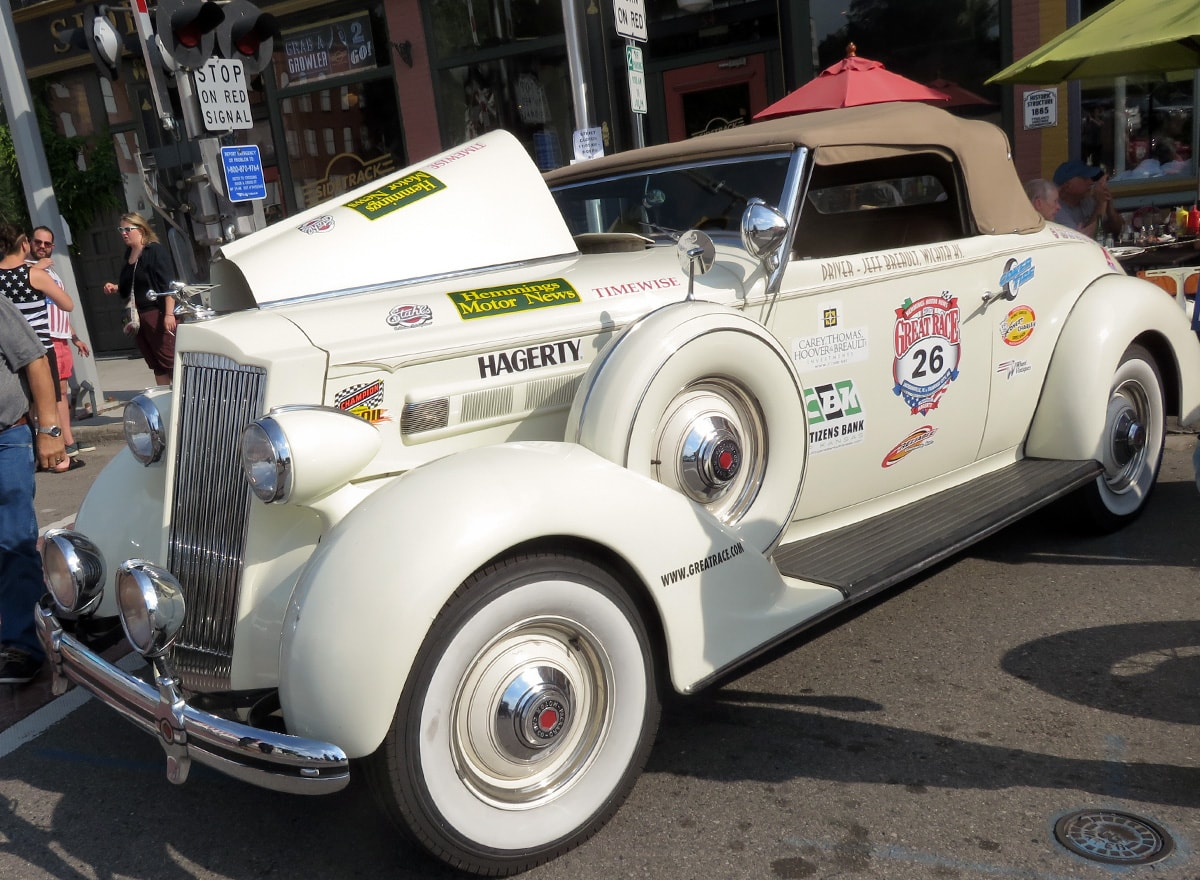 white Packard convertible coupe with half the hood open, white walled tires and running board, and beige convertible top