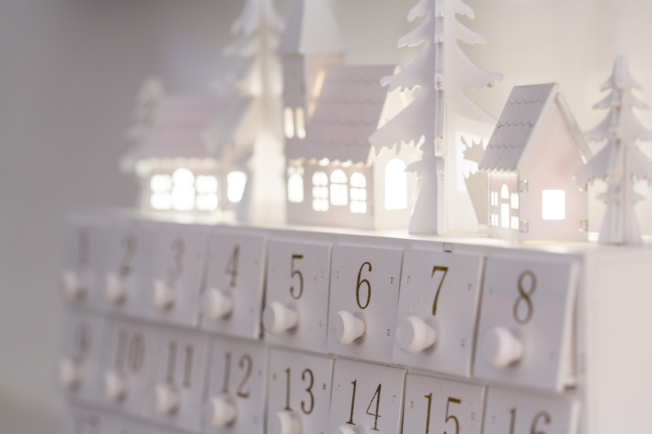 Advent calendar of holiday-lit house, underneath with numbered individual doors to open.