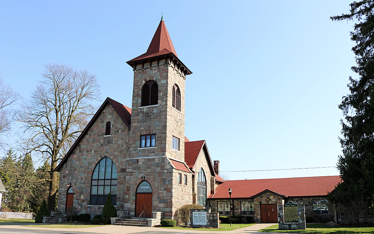 red roofed stone church with red spire, stained glass windows, and inner courtyard.