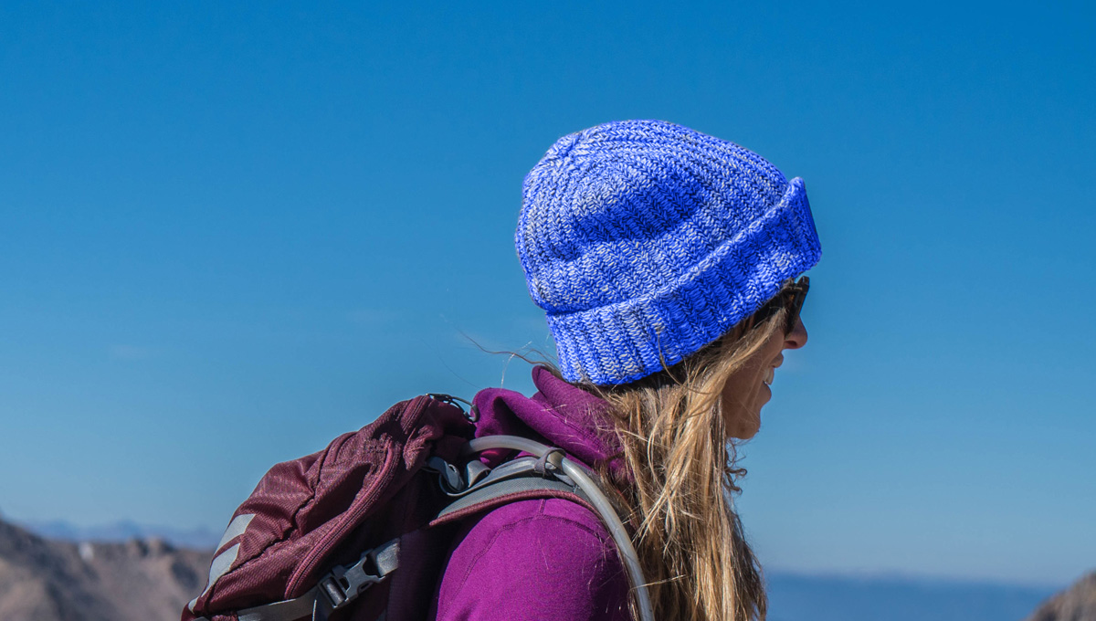 women hiker in the mountains wearing a blue beanie