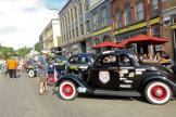 people walk around the classic cars parked in Depot Town, talking with owners and admiring the cars