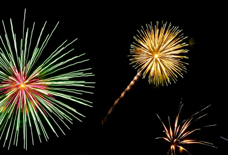 Green, yellow, and blue fireworks burst against a dark sky