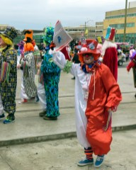 """Clown in red and white costume holding a """"Go Lions"""" newspaper"""