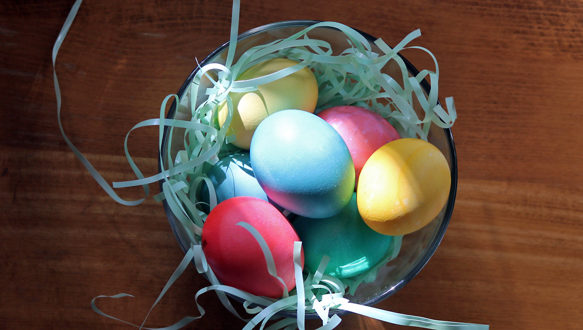 green, yellow, red, and blue Easter eggs arranged in a hand-decorated glass bowl.