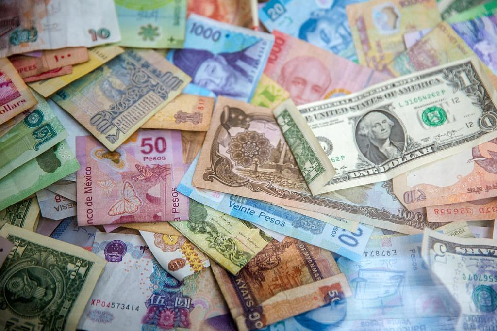 Pink, green, blue, yellow, and brown currency bills laid across a flat surface.