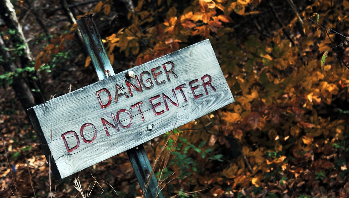 Danger do not enter sign posted on the trail in the woods