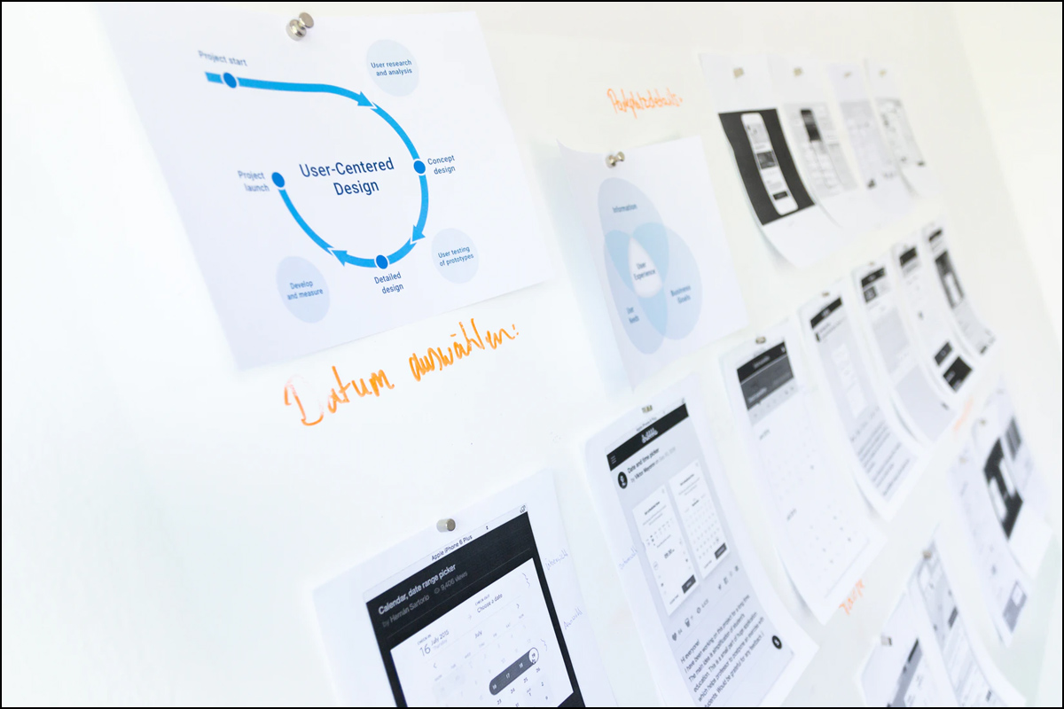 printouts of data services mockups posted on wall showing user tasks.