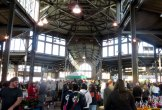 View inside shed at Eastern Market with people, vendors, flowers, and plants