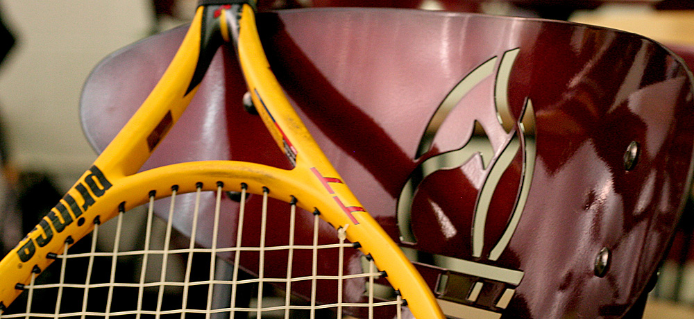 Tennis racquet leaning against chair with Ferris State University logo