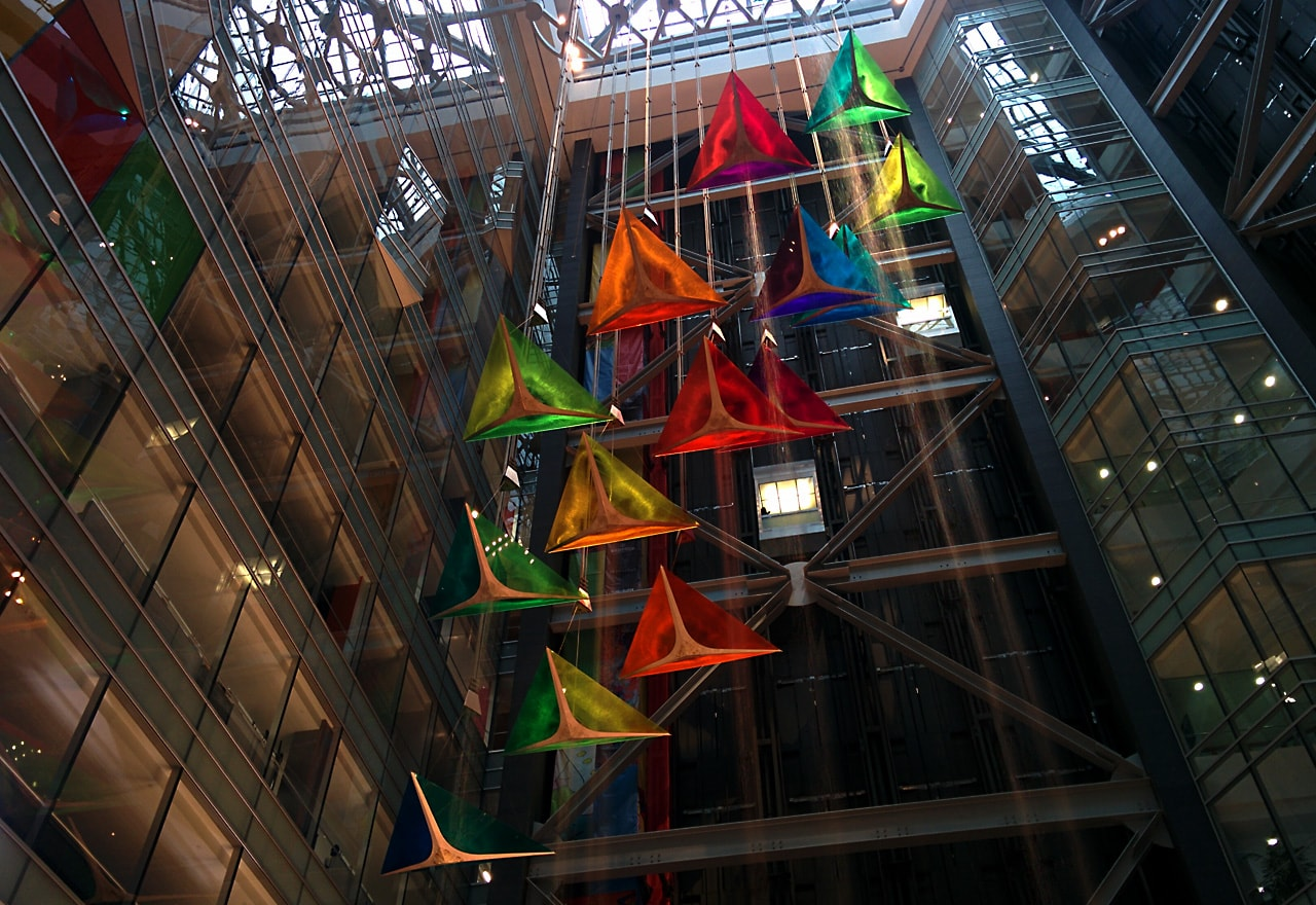 brilliant red, green, and yellow glass kites hanging from the ceiling of a skyscraper