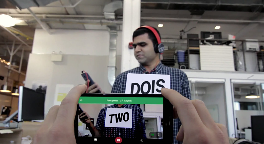 A mobile phone with Google Translate in the foreground, with the word two. In the background, a man holds the a white sign with the word dois.