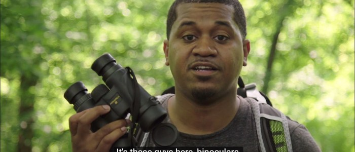 Jason Ward in the woods, holding up his binoculars.