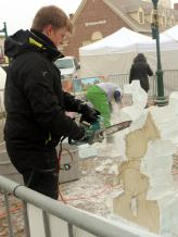 Oakland Community College culinary arts student uses a power saw to carve his ice sculpture