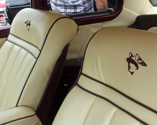 front leather seats displaying Mercury god logo on seat back