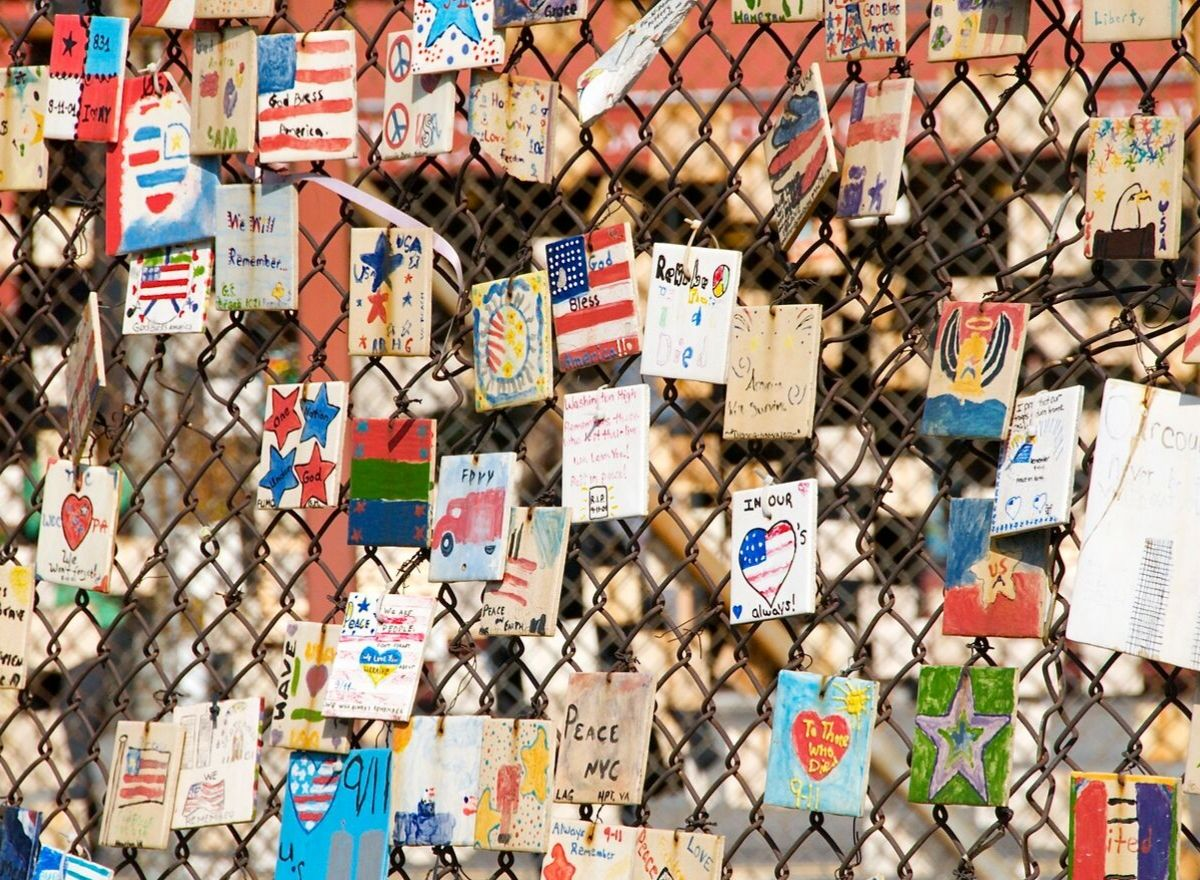 dozens of cards attached to chain link fence, honoring and remembering those who died.