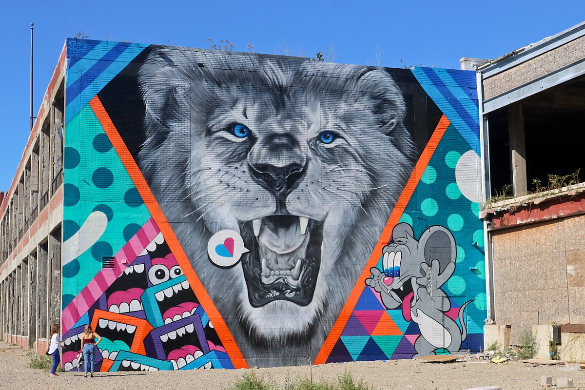 Black and white lion with piercing blue eyes surrounded by whimsical cartoon charaters