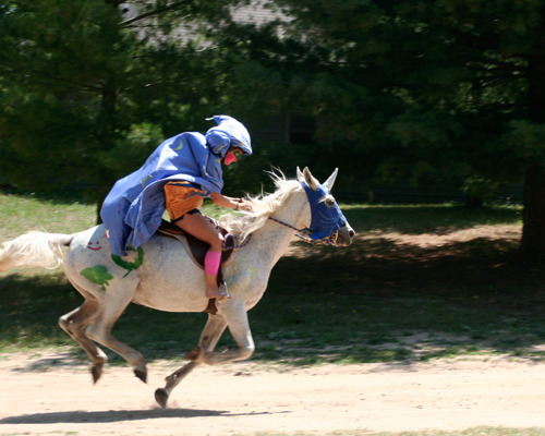 Horse costumed as a unicorn running through Camp Michigania