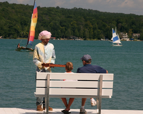 Cookie man delivers freshly baked cookies to two people sitting on the dock