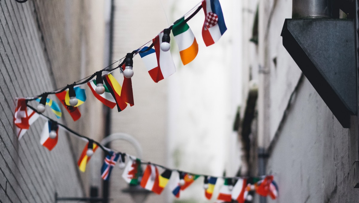 colorful mini flags strewn on a light string between two buildings in a narrow alley.