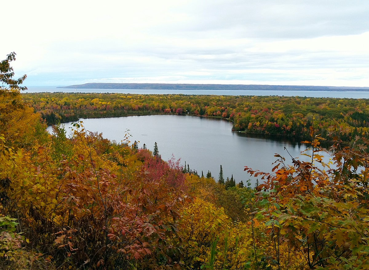 Golden orange, yellow, and red trees surround the blue waters of Spectacle Lake and Lake Superiors.