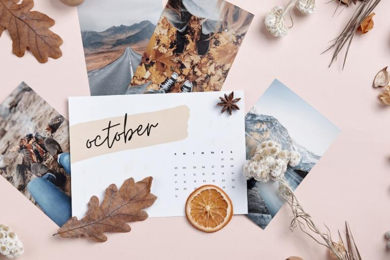Single October calendar page surrounded by dried colorful oak leaves, photos of trips to mountains and lakeshore, and dried flowers on a pale pink background.