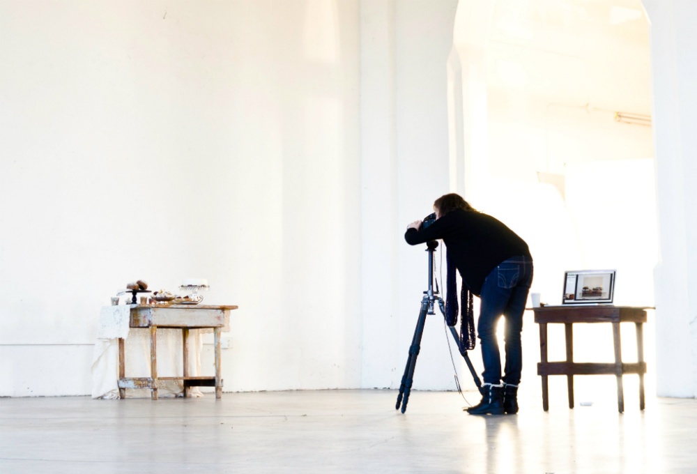 Photographer shooting product with camera on tripod