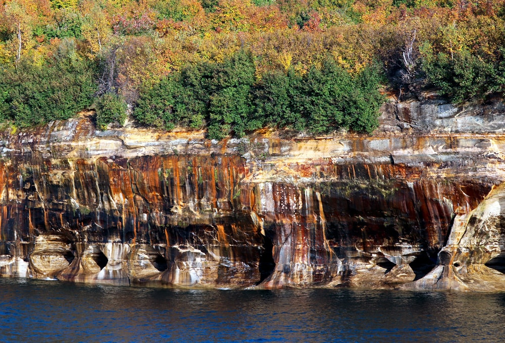 Pictured Rocks National Lakeshore with trees in fall color in background