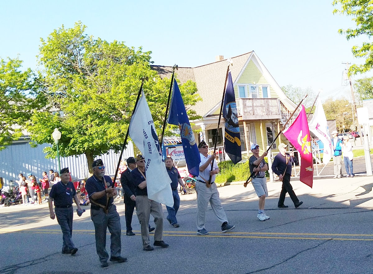 veterans walking down the street, carrying flags from their respective armed services.