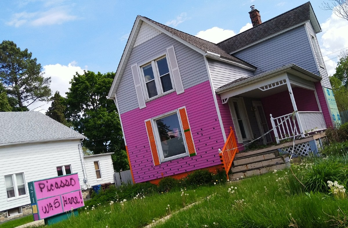 two-story gray house, half-painted with pink sits on an overgrown green lawn in downtown Plymouth.