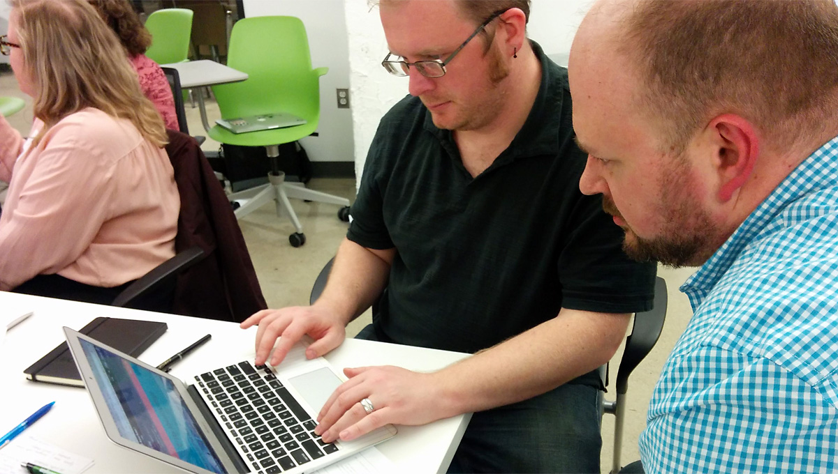 Two attendees seated in front of laptop computer, testing a website with a screen reader