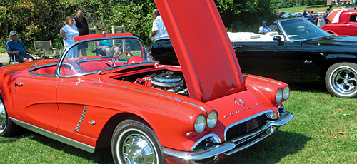 Class red Corvette with it's hood up at a classic car show/cruise