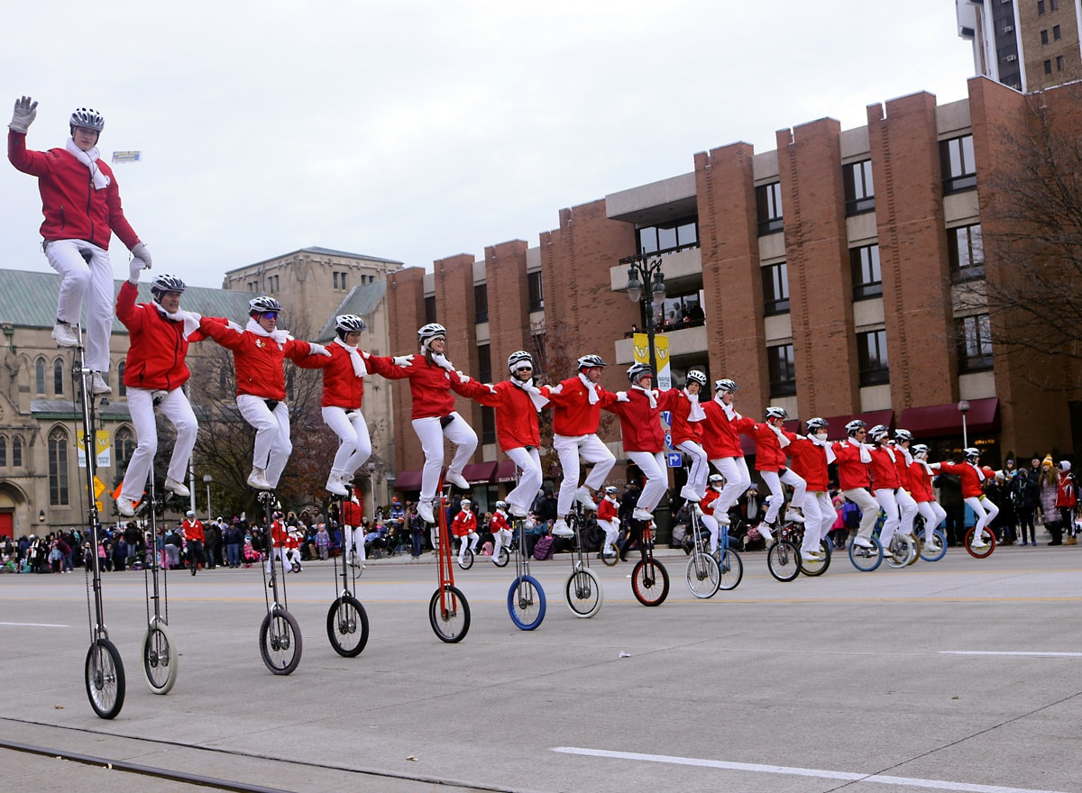 almost two dozen unicyclists dressed in red and white hold each others arms as they cycle in unison.