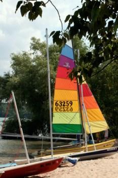Rainbow sail adorns a sailboat on shore