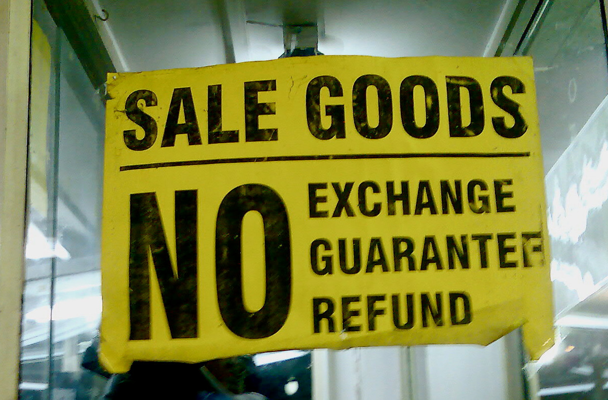 Bright yellow sign with the words, Sale Goods. No exchange, guarantee, refund.