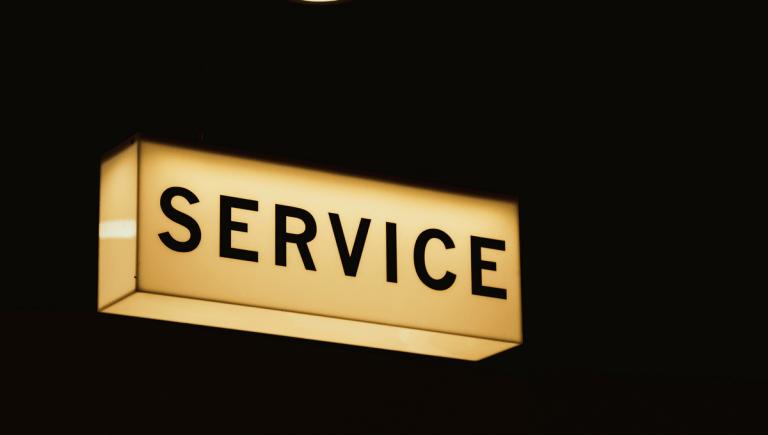 lit up service sign against a dark sky
