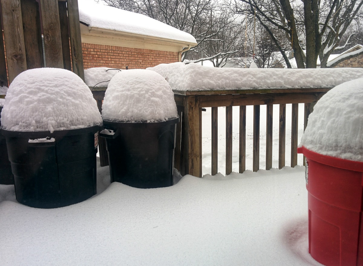 snow almost a foot tall covers the tops of trash cans on a snow-covered wooden deck