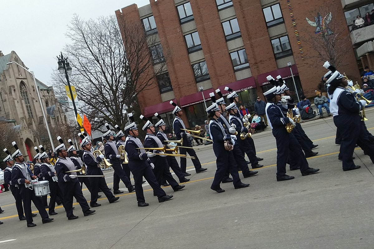 band members dressed in black and white uniforms march down Woodward Avenue.