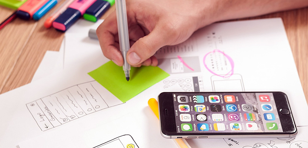 user experience specialist writing on a green post-it note next to design prototypes laid out on a desk