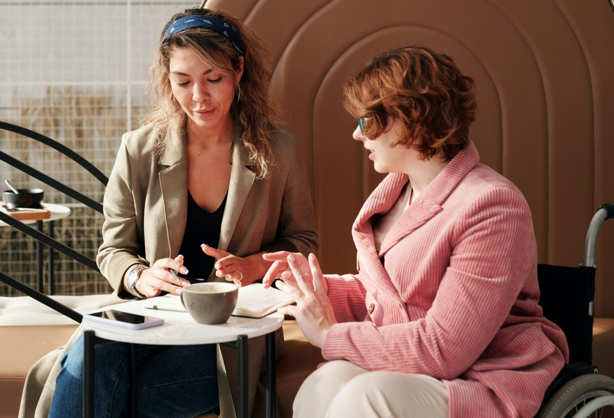 two women seated at a table, in a work meeting.