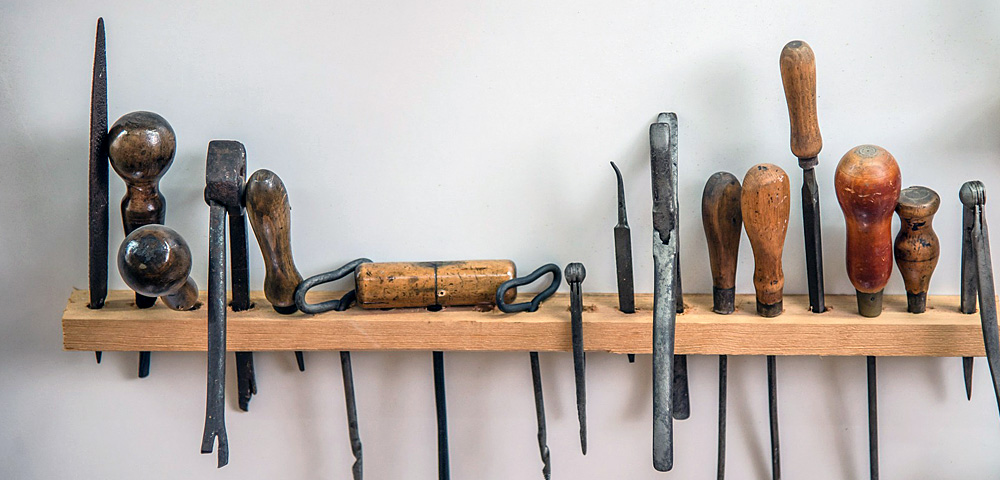woodworking tools hanging on a wall shelf.