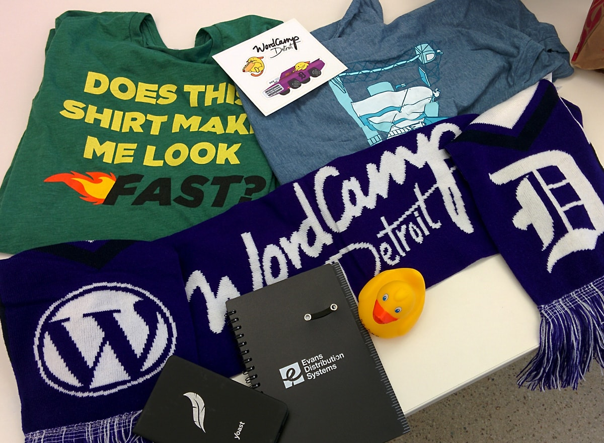 WordCamp Detroit swag including a purple scarf, t-shirts, small notepads, stickers and a small yellow rubber ducky strewn across a table