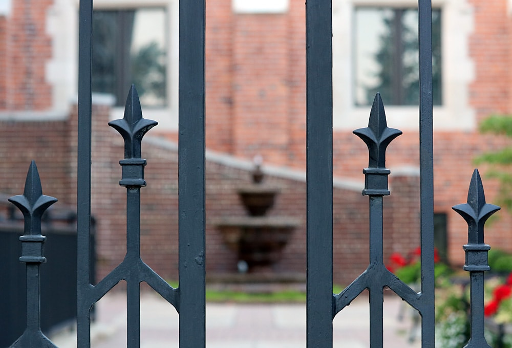 Wrought iron fence with fountain in the background