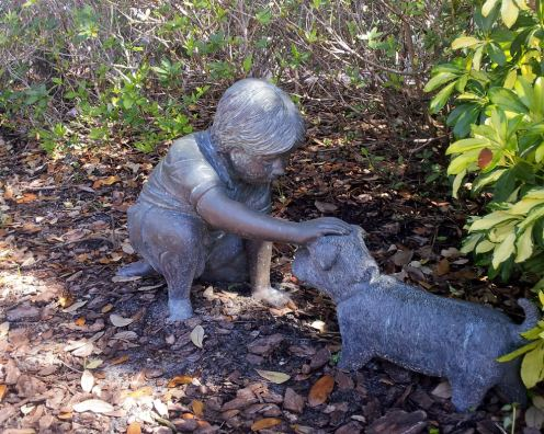 Sculpture: boy petting dog in a park