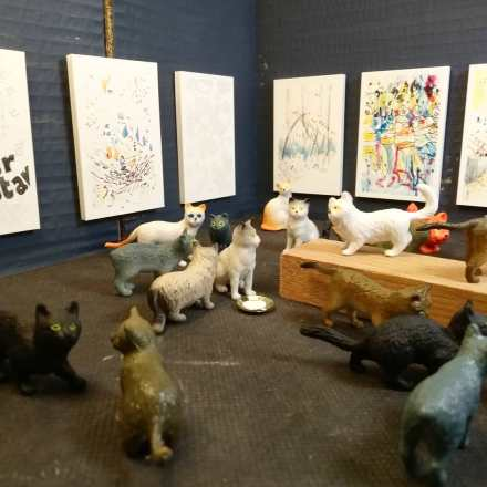 Small plastic cats in a cardboard box gallery looking at paintings by Philip Ryland
