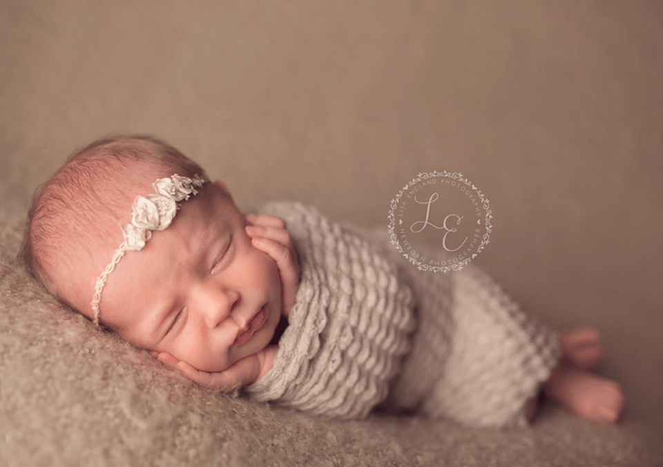 newborn girl laying on side with chin in hands